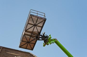 Dacharbeiten mit einer grossen Hebebühne unter blauem Himmel
