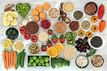 Fresh super food concept with fruit, vegetables, grains, cereals, pulses, seeds, herbs and spice. Foods high in fibre, anthocyanins, antioxidants, smart carbohydrates, minerals and vitamins.