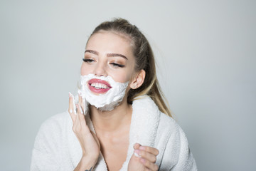 Girl on smiling face in bathrobe covering face with foam for shaving, grey background. Skin care and shaving concept. Woman with face covered with foam. Lady cares about smooth skin