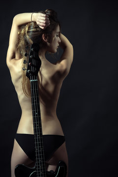 Lady guitarist with sexy appearance naked. Rock star concept. Girl nude and sexy enjoy rock and roll lifestyle, rear view. Girl with nude back stand with guitar neck as spine, black background