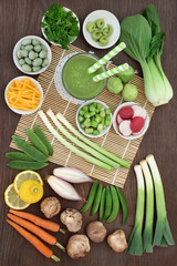 Japanese macrobiotic diet food concept with cold matcha tea, wasabi paste & nuts, fresh vegetables, fruit and   with foods high in antioxidants, fibre, vitamins  minerals. On bamboo and oak, top view.