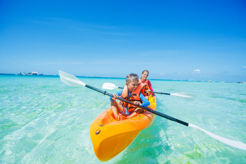 Happy boy and girl kayaking at tropical sea on yellow kayak