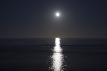 Big full moon is rising above the sea at night. Lunar light reflected on the water. Lunar path. Ocean.