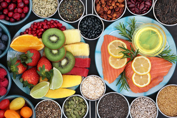Health food for a healthy heart with fresh vegetables, fruit, nuts, seeds, pulses, grains, cereals, herbs and olive oil. High in omega 3 fatty acid, antioxidants, anthocyanins, minerals and vitamins.