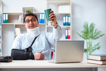 Businessman with broken arm working in office