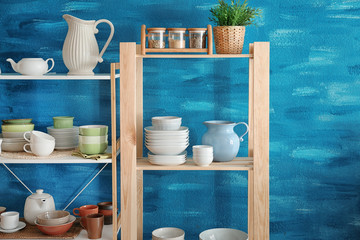 Kitchen shelving with dishes on color wall background