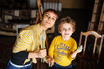 Young mother and her son playing with hands with color on them hold the brushes and laugh