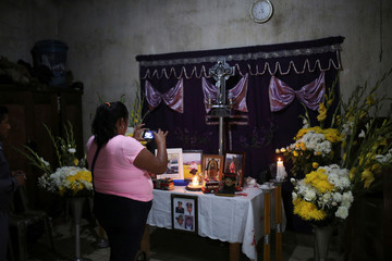 A woman takes pictures of the altar of firefighter Juan Bajxac, 40, who went missing with a colleague while helping people during the eruption of the Fuego volcano, at his home in Alotenango