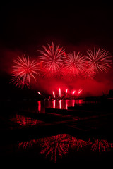Beautiful colorful fireworks display on celebration night Celebration fireworks over the river with cityscape soft focus background at night scene