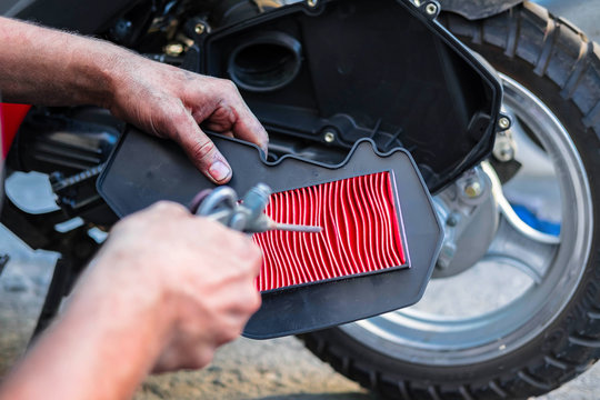 cleaning the air filter, scooter and motorcycle, the employee's hands during maintenance.