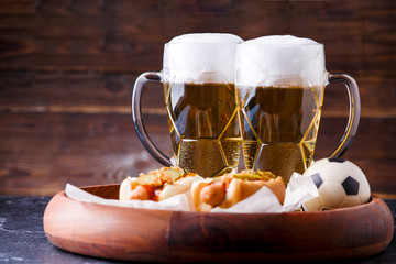 Photo of two mugs of beer and hot dogs on wooden tray with football