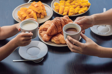 Happy family having breakfast on the balcony. Breakfast table with coffee fruit and bread croisant on a balcony against the backdrop of the big city