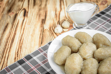 Potato dumplings with stuffed minced meat on a white plate and gravy boat with sour cream on wooden background.