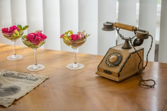 vintage telephone on a wooden table with a flower decoration