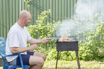 Man cooking meat on barbecue. Young couple making barbecue in their garden. Man cooking meat on barbecue