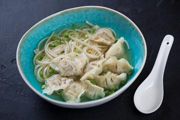 Blue bowl of wonton soup with noodles over black stone background, studio shot