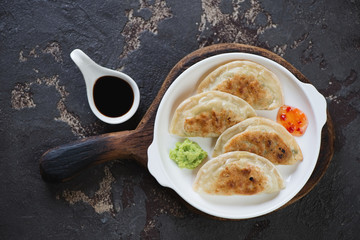 White plate with fried korean potstickers, view from above on a brown stone background, studio shot