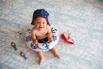Cute baby boy lying down on a tiny inflatable swim ring,  wearing swimsuit shorts and sunglasses, indoor shot