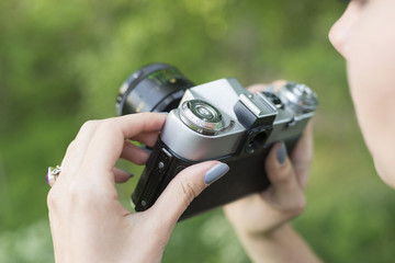 Girl holding a vintage camera on a background of green grass