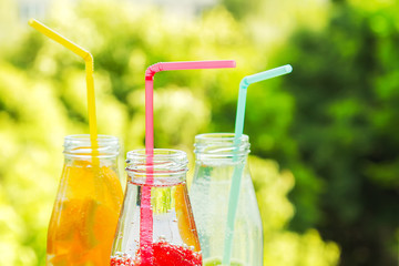 Trio of ice-cold fruit drinks in a summer garden background