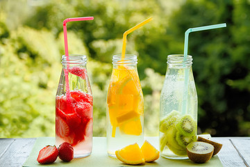 Trio of ice-cold fruit drinks on a wooden grey table on a summer garden background