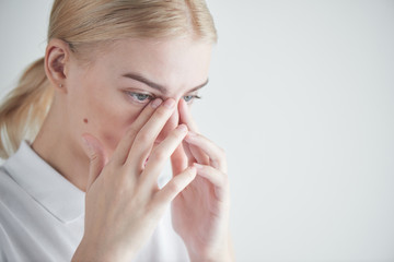 Disease. Eye problems. Girl holding hands near eyes on white background