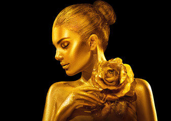 Golden skin woman with rose. Fashion art portrait. Model girl with holiday golden glamour shiny professional makeup. Gold jewellery, accessories