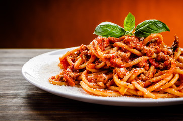 Pasta with meat and tomato sauce on wooden table