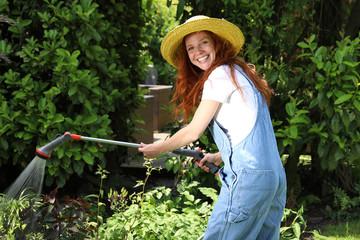 Hübsche rothaarige Frau mit gelbem Strohhut wässert ihren Garten mit einer Handbrause
