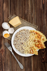 Oatmeal with omelette and cheese on dark wooden table. Healthy breakfast.