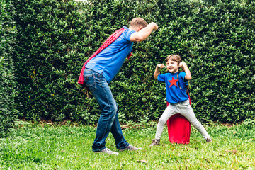 Father with little daughter in superhero costume having fun and playing superheroes together at park outdoors.Love of family and father day concept