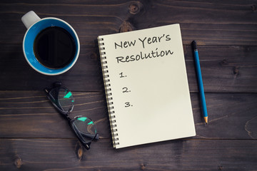 Notebook with 2019 New year's resolution massage, pencil, glasses and cup of coffee on wood background.