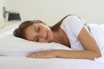 Hübsche junge Frau liegt lächelnd und mit geschlossenen Augen in ihrem Bett