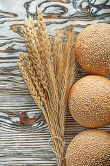 Crusty bread bunch of rye ears on vintage wooden surface