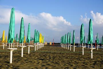 fila di ombrelloni in spiaggia
