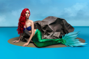 Mermaid with long red hair and the stone on the background