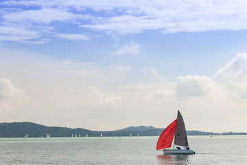Boat with a red sail sailing on the lake under the blue cloudy sky on a sunny day