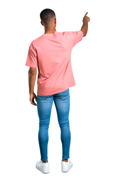 Standing young african american man pointing back with the index finger presenting a product from behind on isolated white background