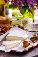 Brie type of cheese. Camembert cheese. Fresh Brie cheese and few slices with whole-grain bun, dry tomatoes, white wine bottle and lilac boquet on the old wooden rustic table. Italian, French cheese.