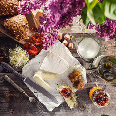 Brie type of cheese. Camembert cheese. Fresh Brie cheese and few slices with bun, dry tomatoes, white wine bottle and glass and lilac on the old wooden rustic table. Italian, French cheese. Top view.