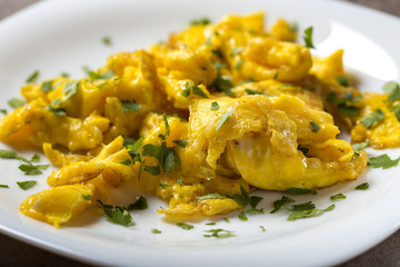 Scrambled eggs on a white plate with green parsley