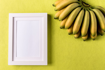 Abstract minimalism colofrul paper background with empty picture frame and banana