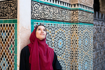 Muslim woman in traditional clothing with red hijab and black dress in front of traditional arabesque decorated wall