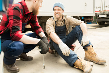 Young handsome male auto technician talking to his bearded colleague and smiling cheerfully while having break in service garage