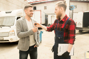 Young bearded auto mechanic giving car keys to happy male client after successful inspection of his vehicle in service garage