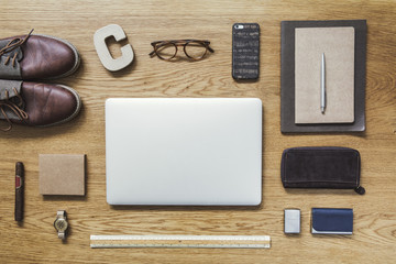 Modern composition of flat lay on wooden desk with laptop, phone, shoes  notebook, glasses and office accessories. Creative desk  of traveler.
