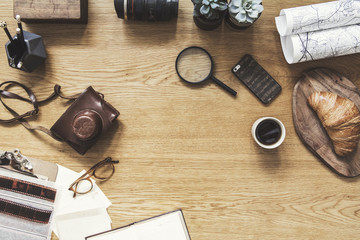 Stylish composition of flat lay on wooden desk with succulent, map, cup of coffee, croissant, phone, notebook, camera and office accessories. Creative desk of freelancer. Copy space for inscription.