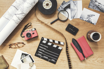 Modern composition of flat lay on wooden desk with  map, photo plate, cup of coffee, phone, notebook, photos, camera and office accessories. Creative desk of freelancer.