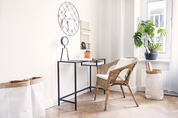 Modern scanidinavian interior of home office with glass table, design clock paper bags and plants. Stylish space with wooden brown parquet.
