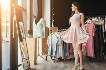 Smiling woman trying on dress at mirror